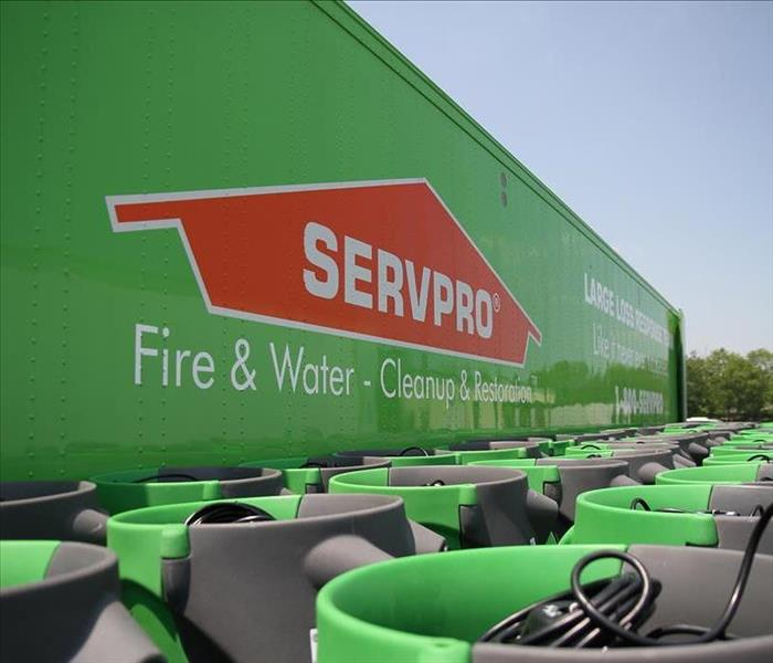 Big green SERVPRO truck with several green air movers in front of the truck.