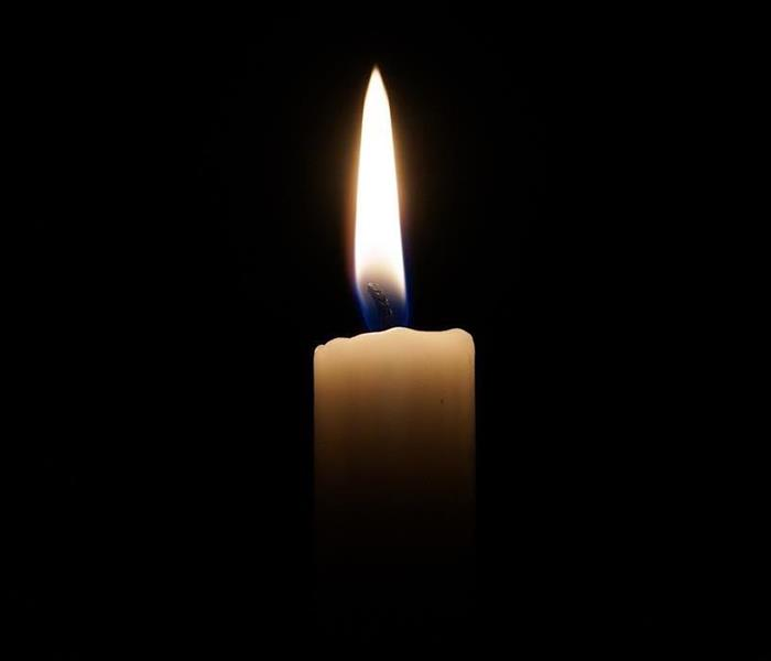 White candle with a flame with a black background.